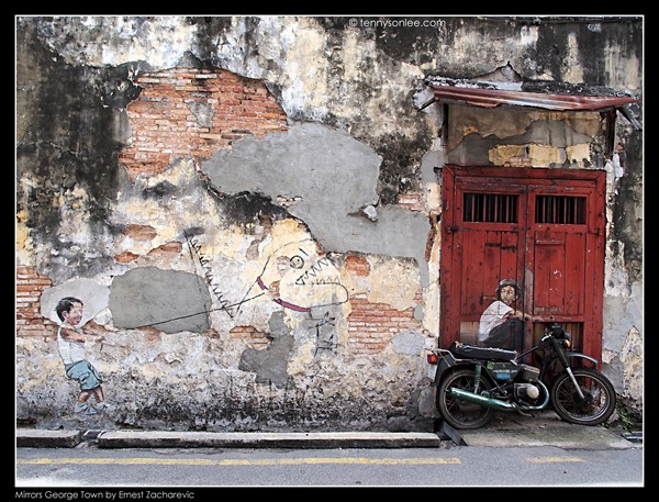 Ernest Zacharevic Mirrors George Town mural - Little boy with pet dinosaur chasing boy on bike