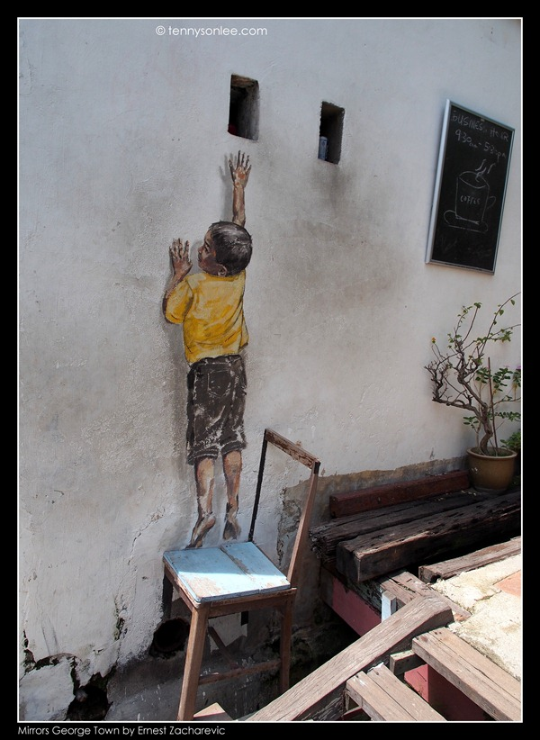 Ernest Zacharevic Mirrors George Town mural - reaching up